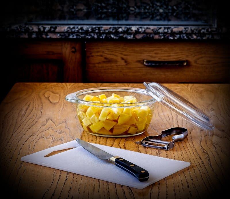 Nóż, tnąca deska, obieraczka i puchar z rżniętymi grulami na kuchennym stole, zdjęcie stock
