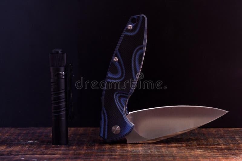 Nóż w komplikującej pozycji i małej latarce zdjęcie royalty free