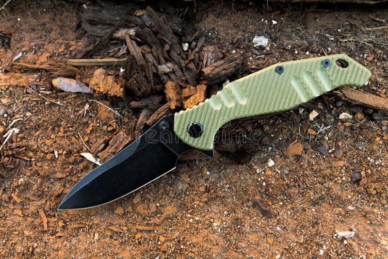 Nóż z czarnym ostrza i zieleni handl stary drewna militate fotografia stock