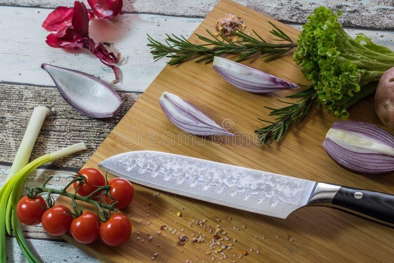 Nóż z zdrowym jedzeniem - warzywa, cebula, sałatka, pomidory, grula umieszczająca na tnącej desce z drewnianego tła odgórnym wido obraz stock