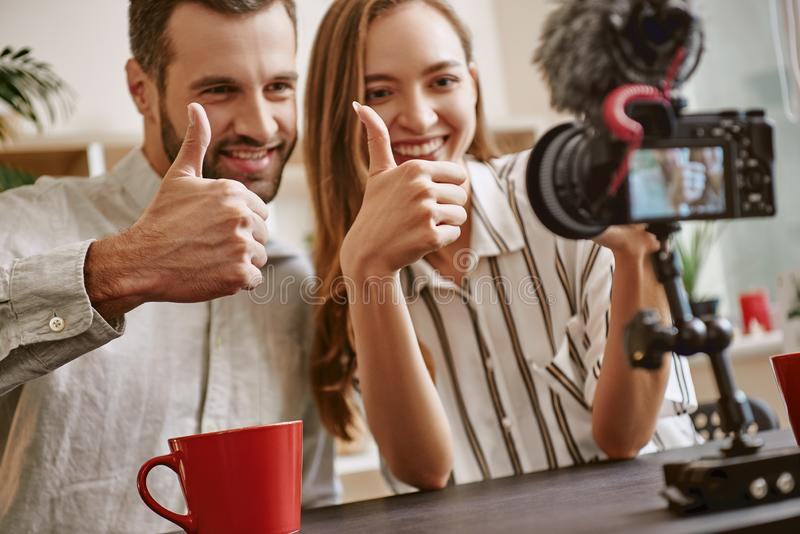 Nós amamo-lo! Pares de bloggers alegres e de sorriso na câmera ao fazer um vídeo novo para o blogue imagem de stock