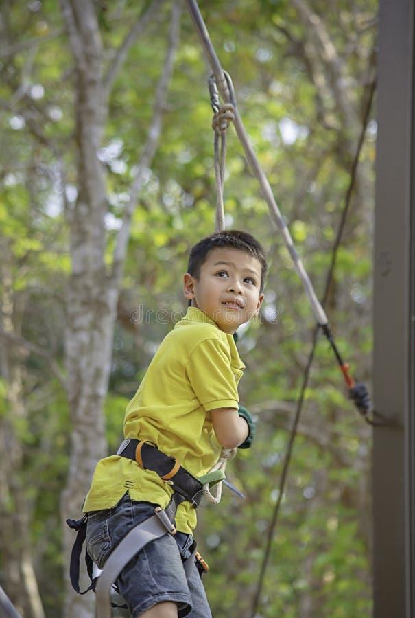 Nós do menino do Asean a corda e sorriso felizmente na árvore obscura do fundo da aventura do acampamento fotografia de stock royalty free