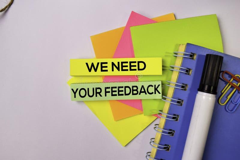 Nós precisamos seu feedback nas notas pegajosas isoladas no fundo branco foto de stock
