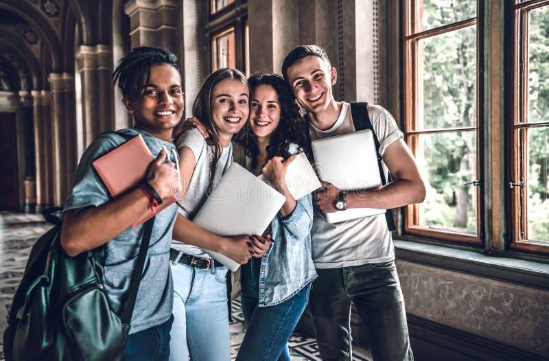 Nós que estudamos junto e amigos para sempre! Quatro estudantes felizes que guardam livros, portáteis e sorrindo ao olhar a câmer imagem de stock royalty free