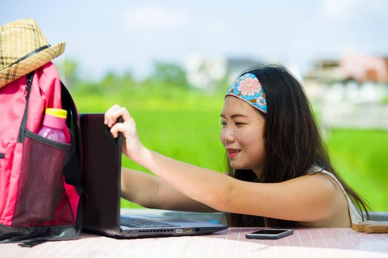 Nômada digital asiático bonito e feliz novo ou trabalhos em rede coreanos da mulher do turista fora com o sorriso do laptop alegr imagens de stock