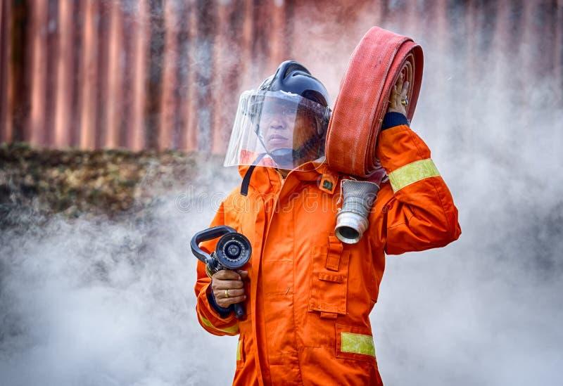 Nöd- brandräddningsaktionutbildning, brandmän i likformig, bär royaltyfria foton