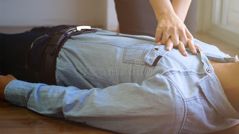 N?d- CPR p? en man med regelbundet ?terkommande hj?rtinfarkt, brukshandpump p? br?stkorgen f?r f?rsta hj?lpen ?teruppv?ckandeproc arkivfoton