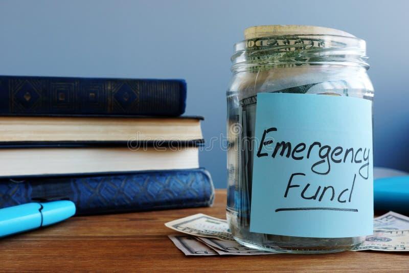 Nöd- fond som är skriftlig på en krus med pengar royaltyfri bild