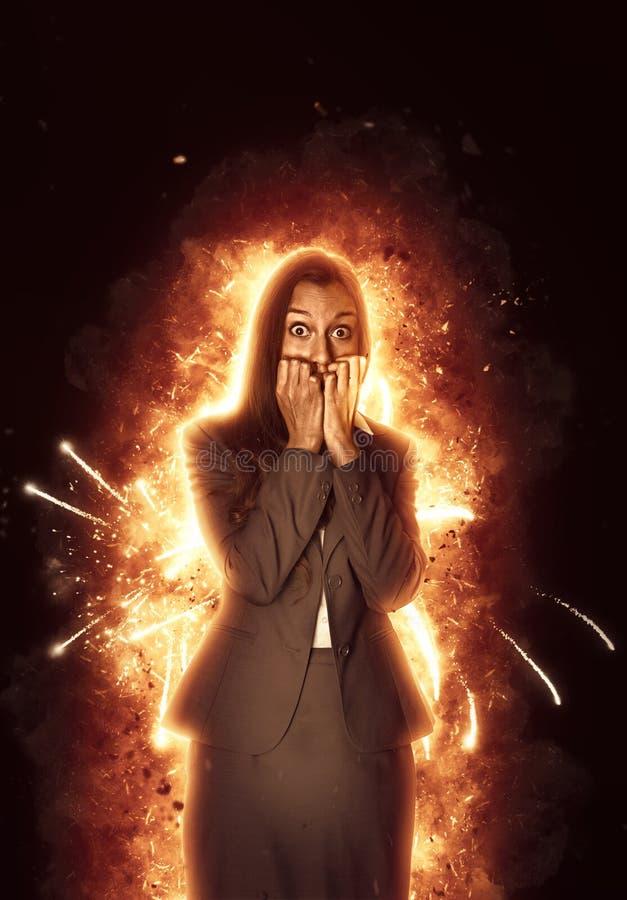 Nöd slågen affärskvinna som omges av flammor royaltyfria foton