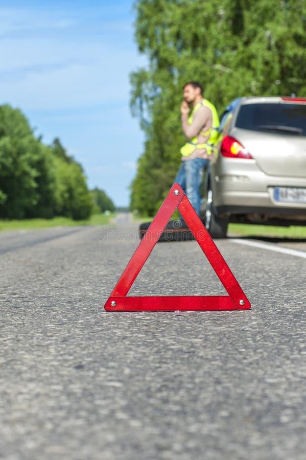 Nöd- tecken på vägrenen, chauffören med telefonen och den brutna bilen royaltyfri fotografi