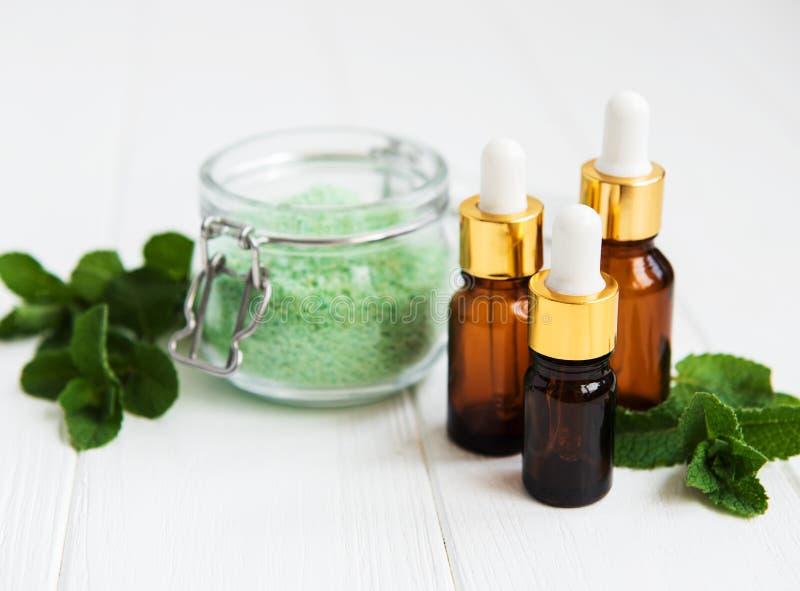 Nödvändig aromolja med den salta massagen och mintkaramellen royaltyfri fotografi