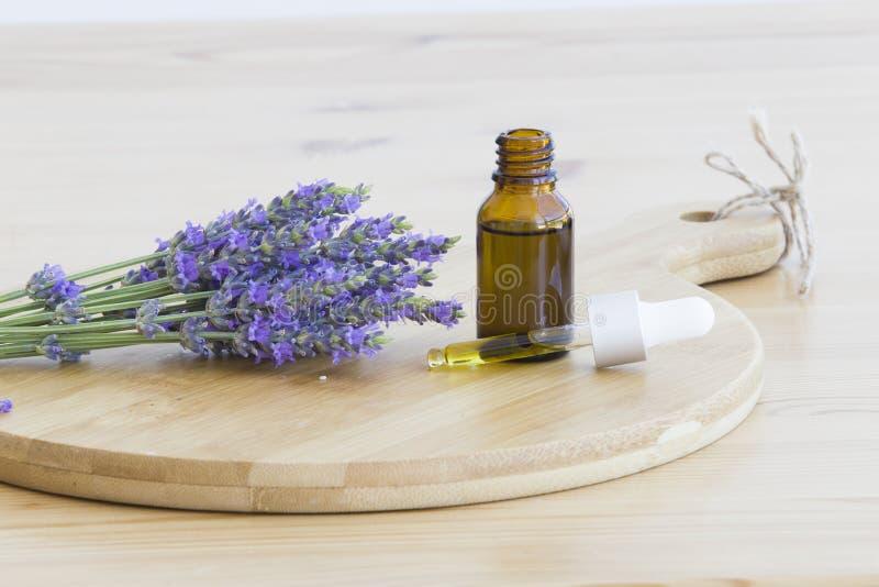 Nödvändig lavendelolja i flaskan med droppglassen på träskrivbordet Horisontaln?rbild royaltyfri foto