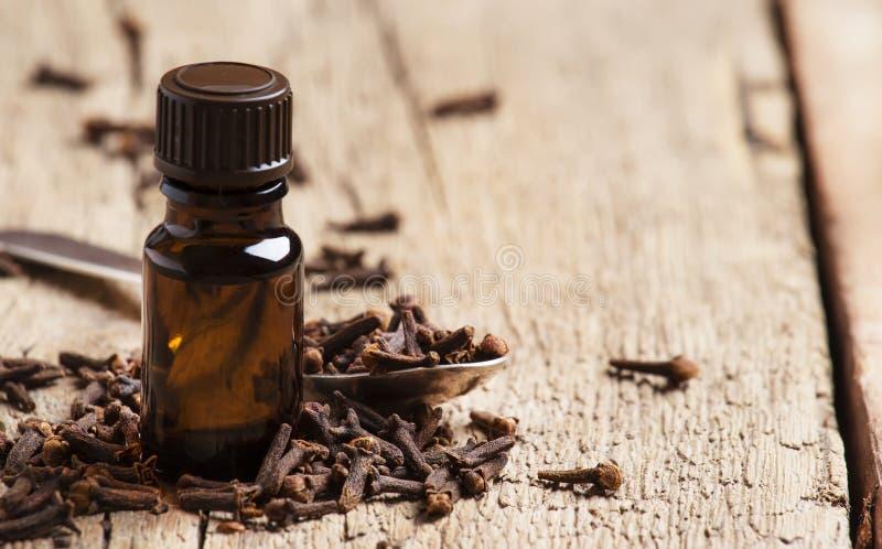 Nödvändig olja av kryddnejlikor, brun flaska, gammal träbakgrund, selektiv fokus royaltyfria bilder