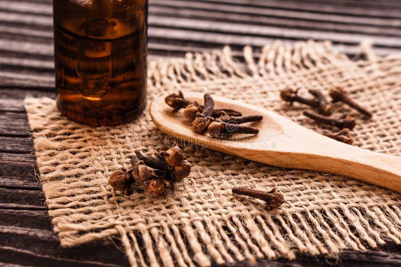 Nödvändig olja av kryddnejlikor på en trälantlig bakgrund royaltyfria bilder
