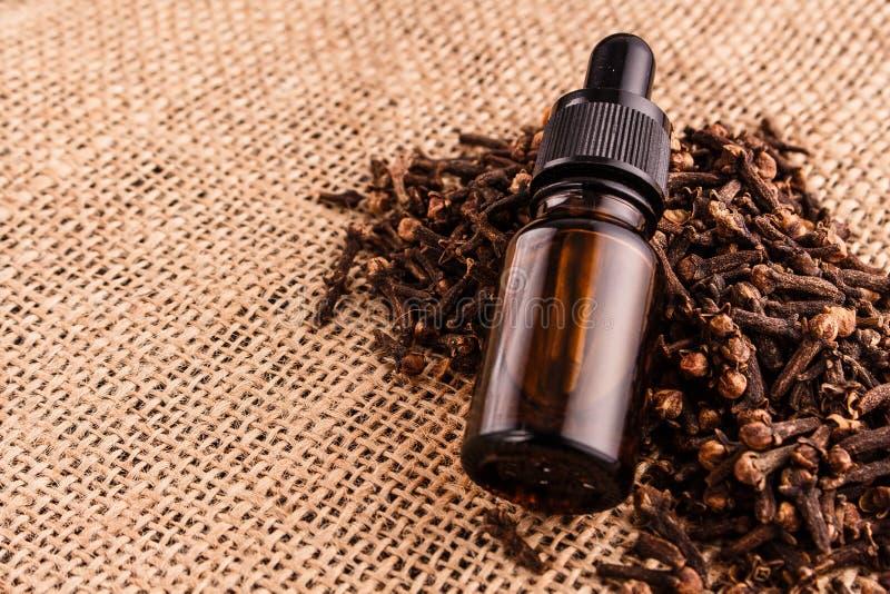 Nödvändig olja av kryddnejlikor på en trälantlig bakgrund fotografering för bildbyråer