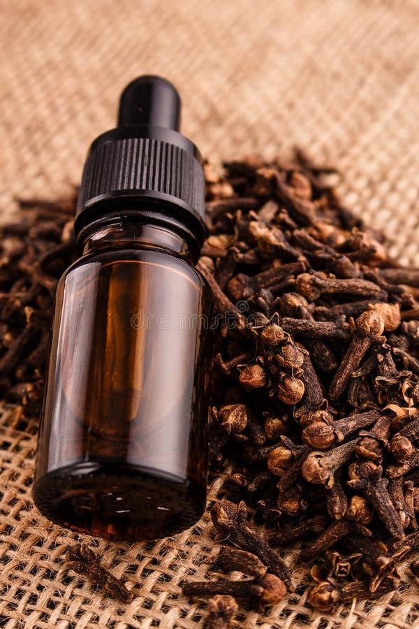 Nödvändig olja av kryddnejlikor på en trälantlig bakgrund royaltyfri bild