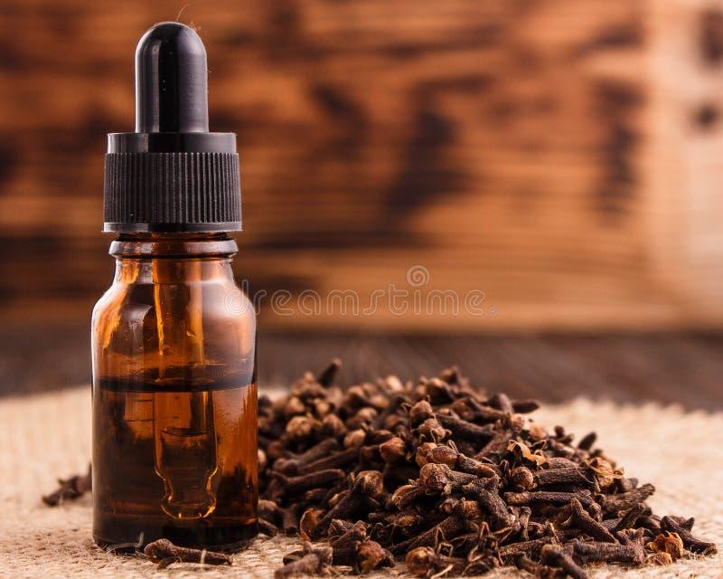 Nödvändig olja av kryddnejlikor på en trälantlig bakgrund arkivfoton