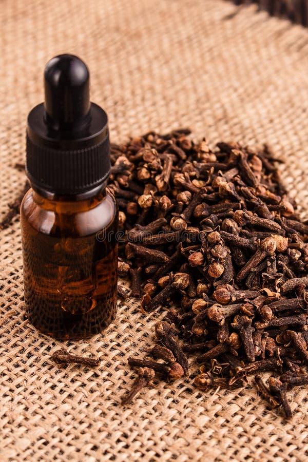 Nödvändig olja av kryddnejlikor på en trälantlig bakgrund royaltyfria foton