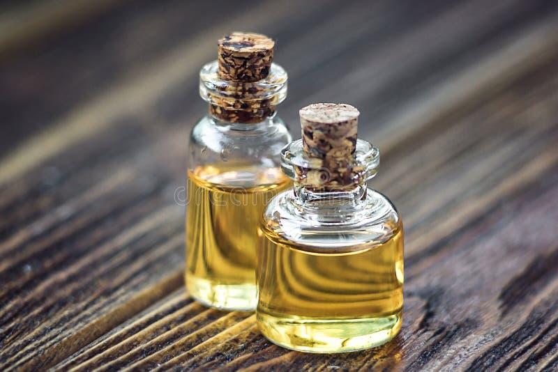 Nödvändig olja för ren organisk arom i glasflaskan som isoleras på träbakgrundsskönhetbehandling Doftande olje- brunnsortbegrepps royaltyfri bild