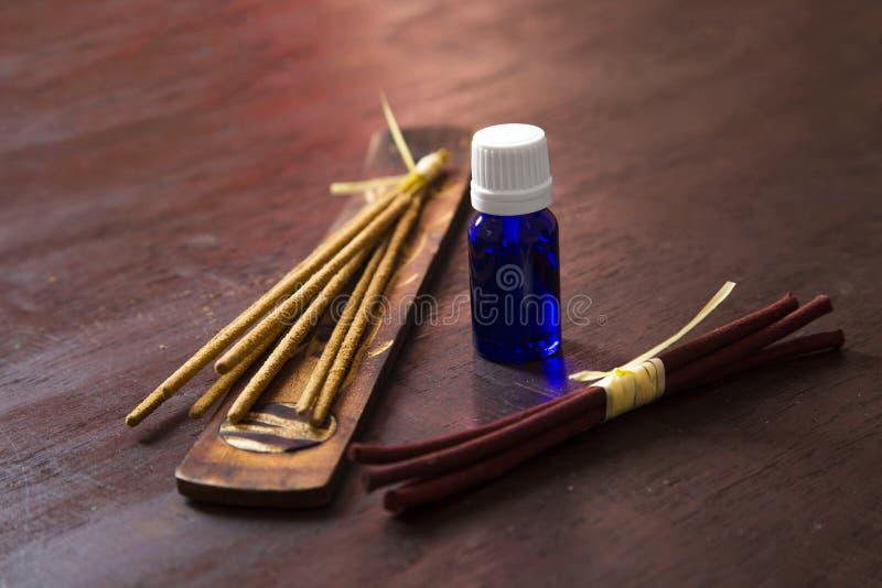 Nödvändig olja med rökelse på en trätabell arkivbild