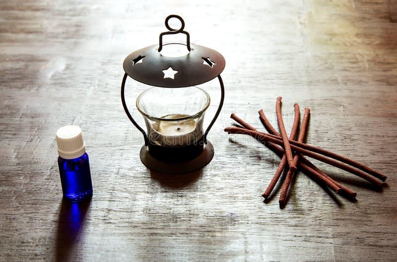 Nödvändig olja, stearinljushållare med rökelse på en trätabell royaltyfria foton