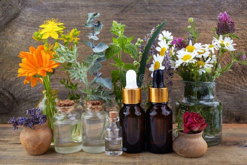 Nödvändiga oljor med örter och blommor på trätabellen arkivbild