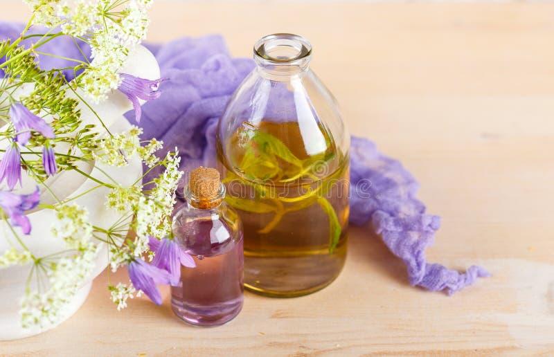 Nödvändiga oljor och lösa blommor royaltyfri bild