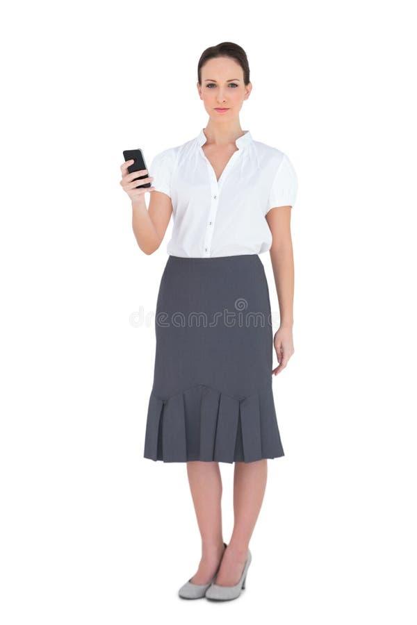 Nöjd affärskvinna som rymmer hennes telefon royaltyfri fotografi