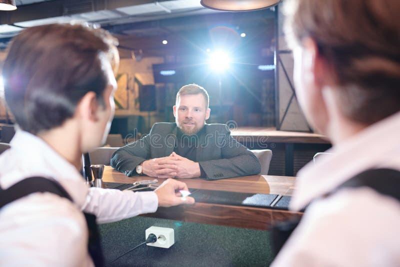 Nöjd affärsman som gör beställning på stångräknaren arkivfoto