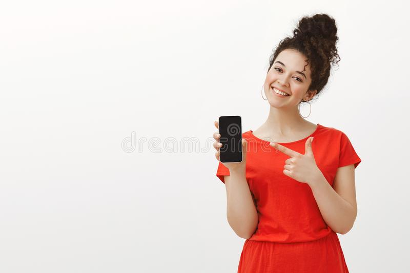 Nöjd bekymmerslös flickvän i den gulliga röda klänningen som visar smartphonen och i huvudsak ler med det vippade på huvudet, med arkivfoto