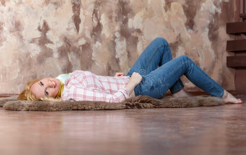 Nöjd blond flicka som ligger på en päls på golvet royaltyfri foto