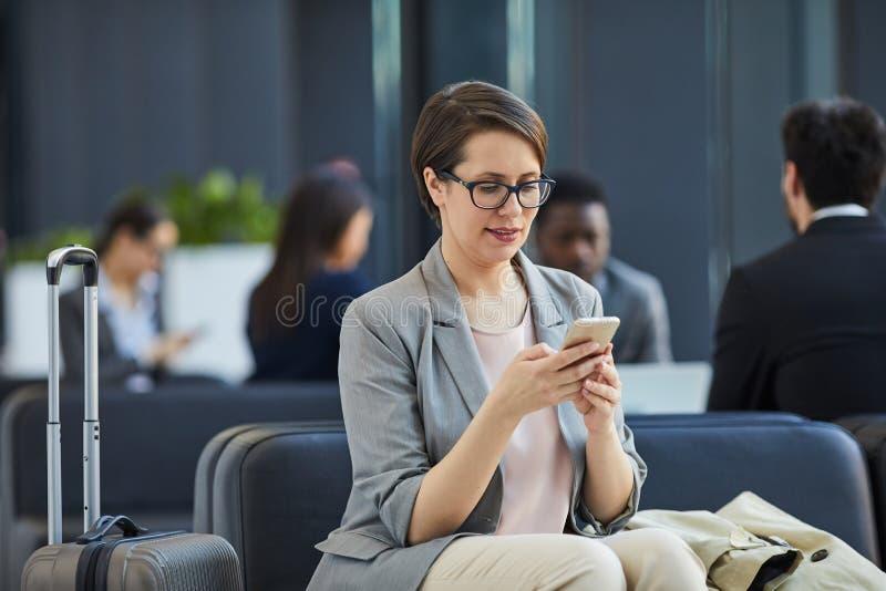 Nöjd dam som kontrollerar budbärare i flygplats arkivbild