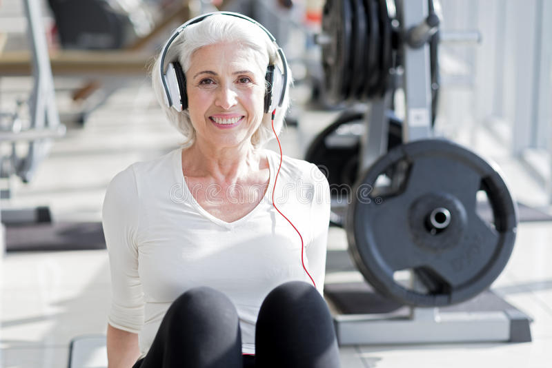 Nöjd hög kvinna som lyssnar till musik efter genomkörare arkivbilder