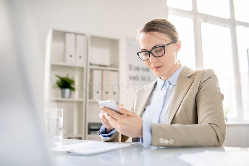 Nöjd kontorsanställd som använder grejen på arbetsplatsen royaltyfri foto