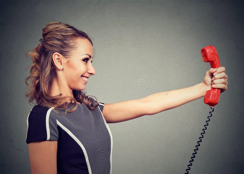 Nöjd kvinna med den röda telefonluren royaltyfria foton