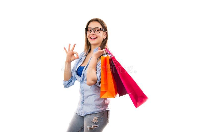 Nöjd kvinna med shoppingpåsar som visar reko gest arkivfoton