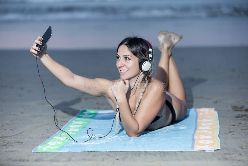 Nöjd kvinna som poserar för selfie på stranden royaltyfri bild