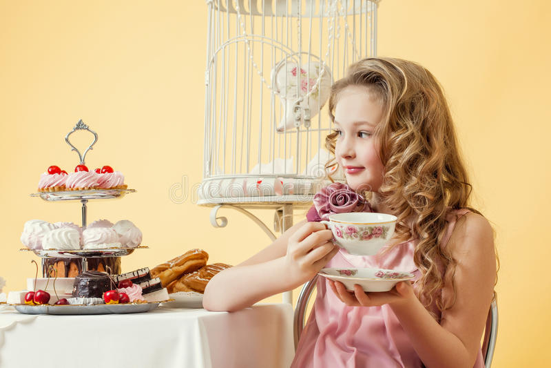 Nöjd liten flicka som dricker te med kakan royaltyfri bild