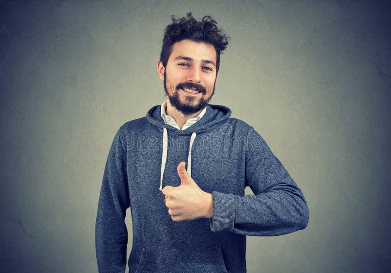 Nöjd lyckad hipster som gör en gest på grå färger arkivfoto