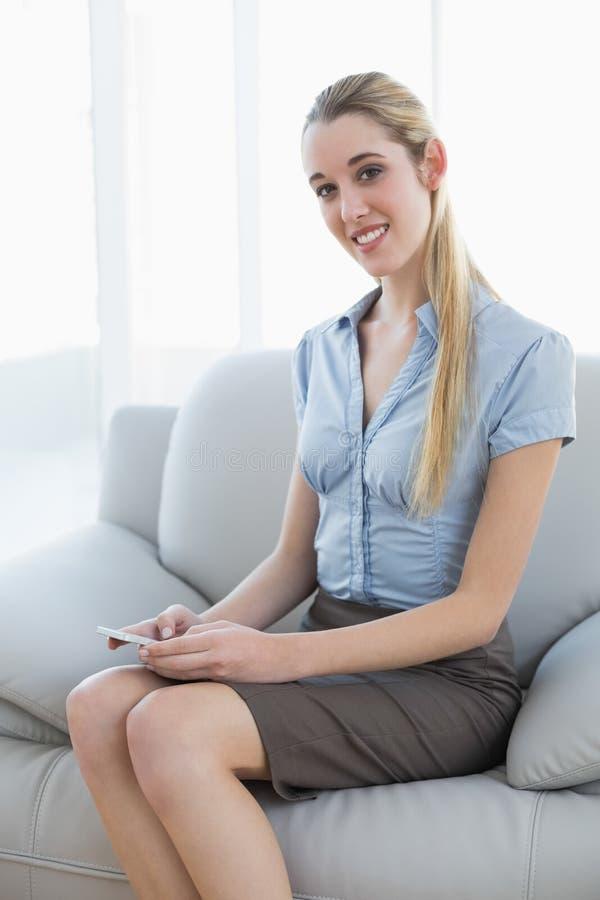 Nöjd nätt affärskvinnamessaging med hennes smartphonesitti royaltyfri foto