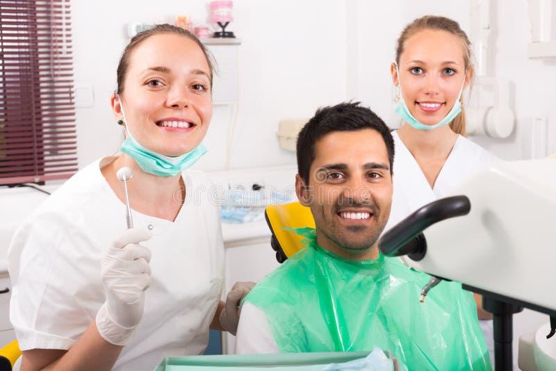 Nöjd patient på tandläkarekontoret royaltyfria bilder