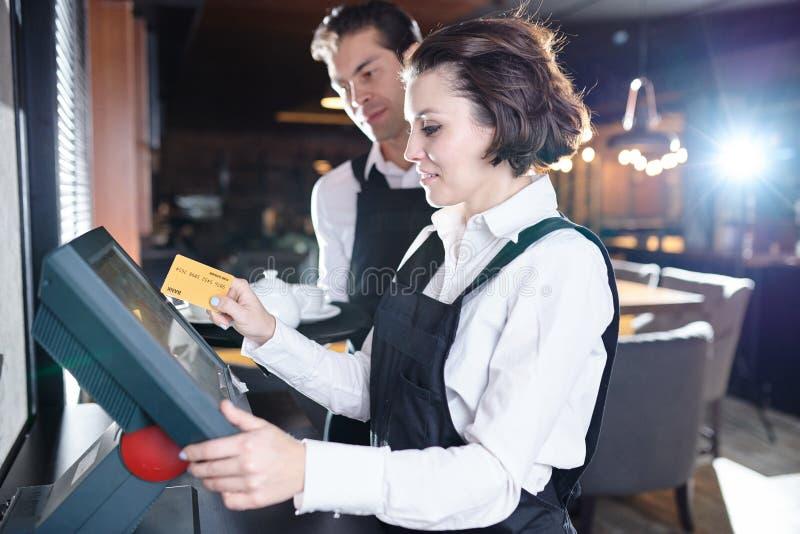 Nöjd servitris som nallar kortet till och med pos.-terminalen arkivbilder
