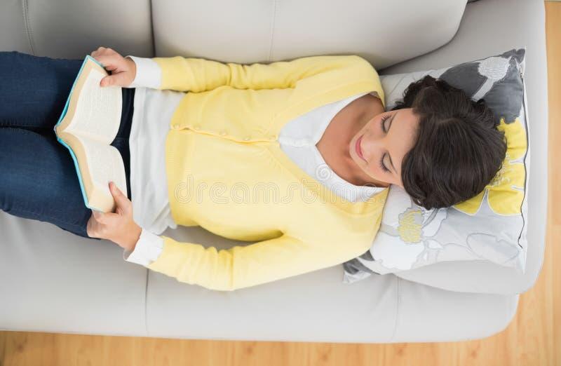 Nöjd tillfällig brunett i den gula koftan som läser en bok royaltyfria bilder