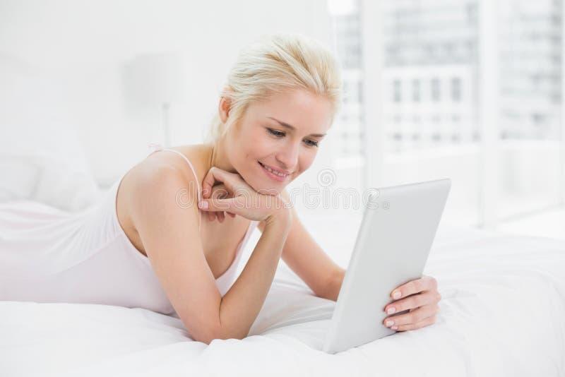 Nöjd tillfällig ung blond användande minnestavlaPC i säng arkivfoto