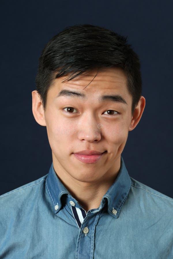 Nöjd ung asiatisk man som ser kameran royaltyfri bild