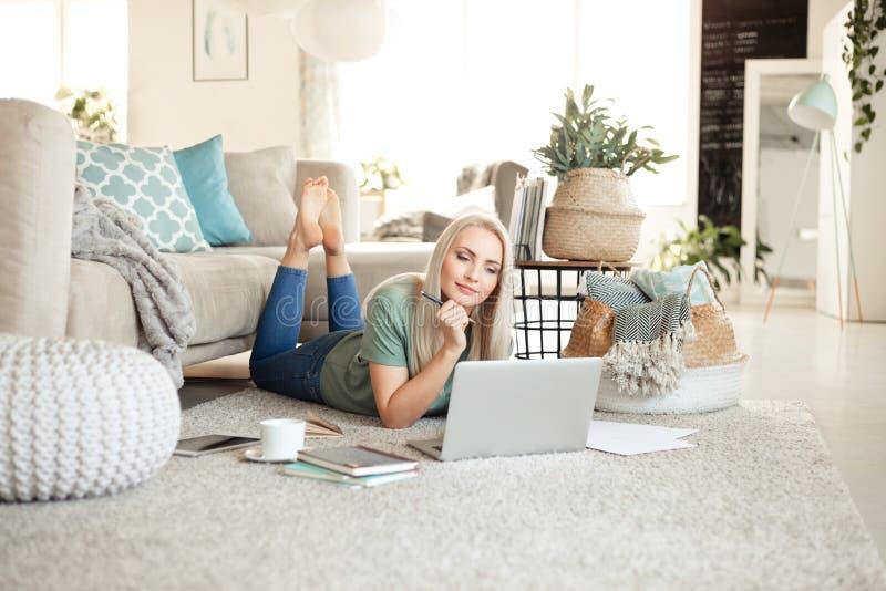 Nöjd ung kvinna som använder en bärbar dator i vardagsrum royaltyfria foton