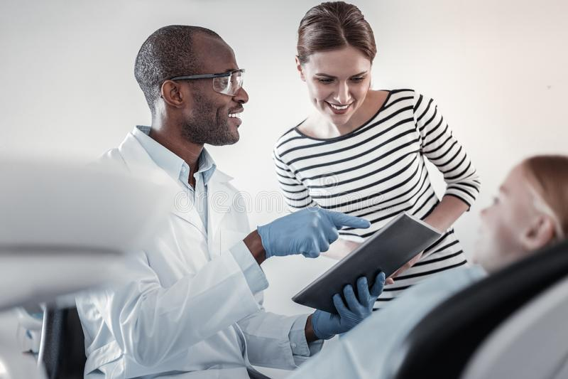 Nöjd ung kvinna som lyssnar till tandläkaren av hennes unge arkivfoto