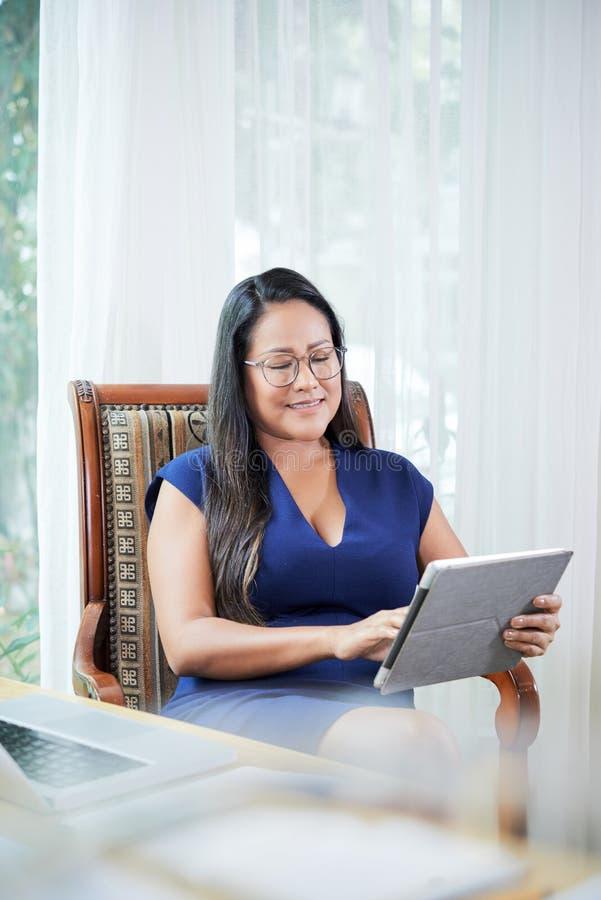 Nöjd vuxen affärskvinna med minnestavlan i regeringsställning royaltyfri bild
