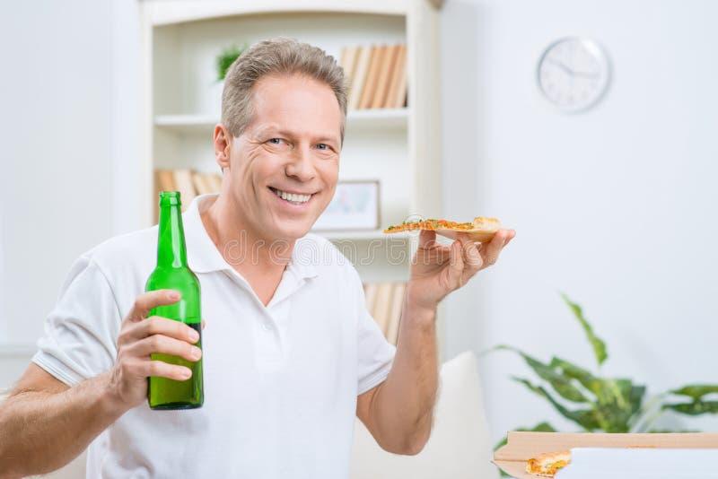 Nöjd vuxen man som dricker öl arkivfoton