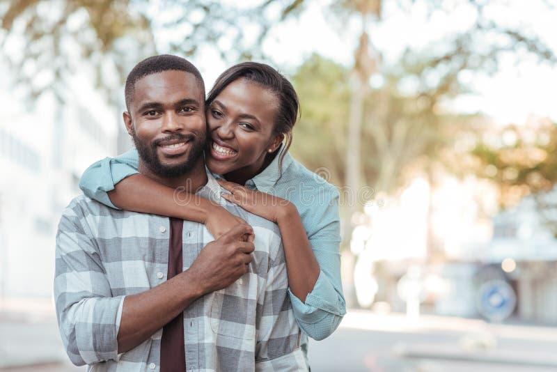Nöjda afrikanska par som tillsammans står utanför på en solig dag royaltyfri fotografi